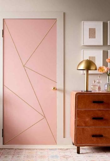 Detalle de trasera de puerta en color y con remaches junto aparador color cuero y lamparita dorada_visto en Marthastewart.com por Elyse Moody